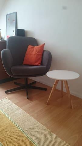 Der bequeme, zum Sofa passende Drehsessel mit Beistelltischchen.