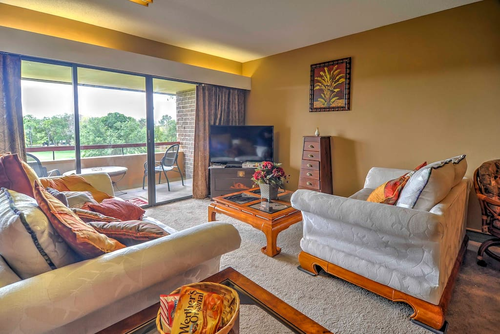 The comfortable, vibrant living room filled with natural light pouring from the patio door windows.