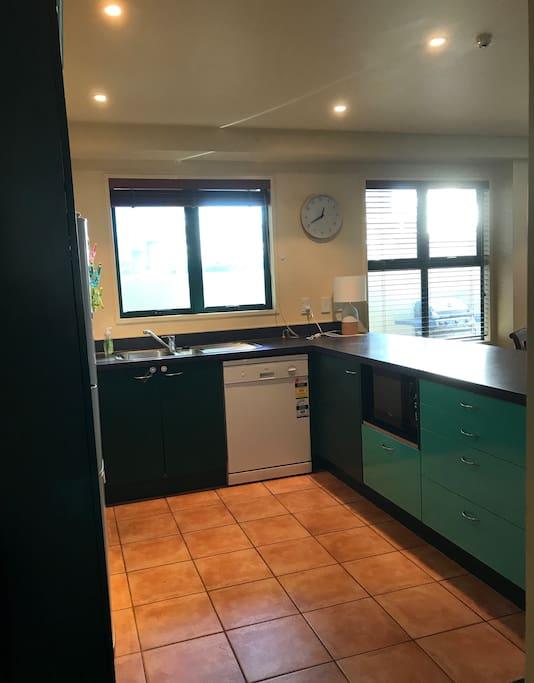 Kitchen with stove top, oven, rangehood, dishwasher, microwave, pots & pans, utensils, cutlery etc.
