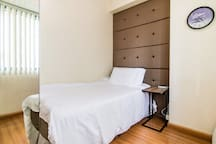 Ground floor bedroom with a single bed with very comfortable memory foam topper on top of the spring mattress bed. Extra floor mattress is available and can fit inside the room. USB chargers at your arms reach.