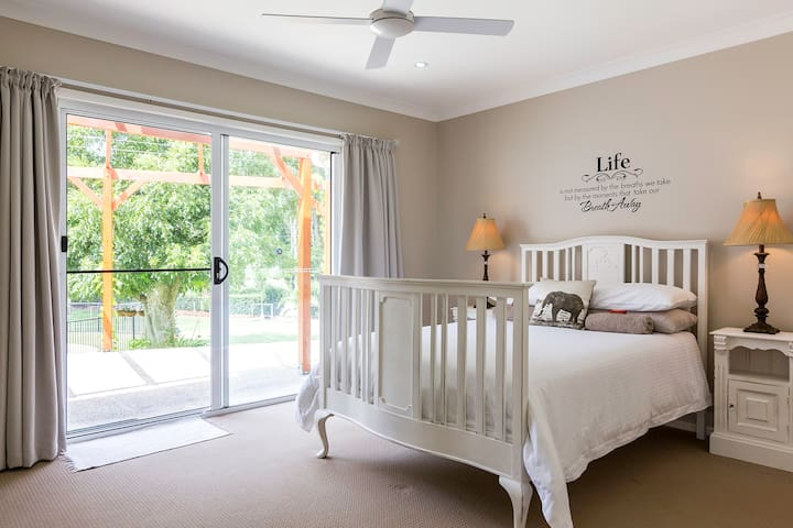 The main bedroom has a Queen bed and opens up onto your own private patio overlooking the manicured gardens and swimming pool.