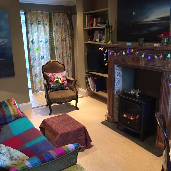 Cosy sitting room with original art work, interesting books, Smart TV, dining table and chairs, fireplace with log effect electric fire, glazed door on to garden, large window with pretty view of farm smallholding and Blackdown Hills beyond