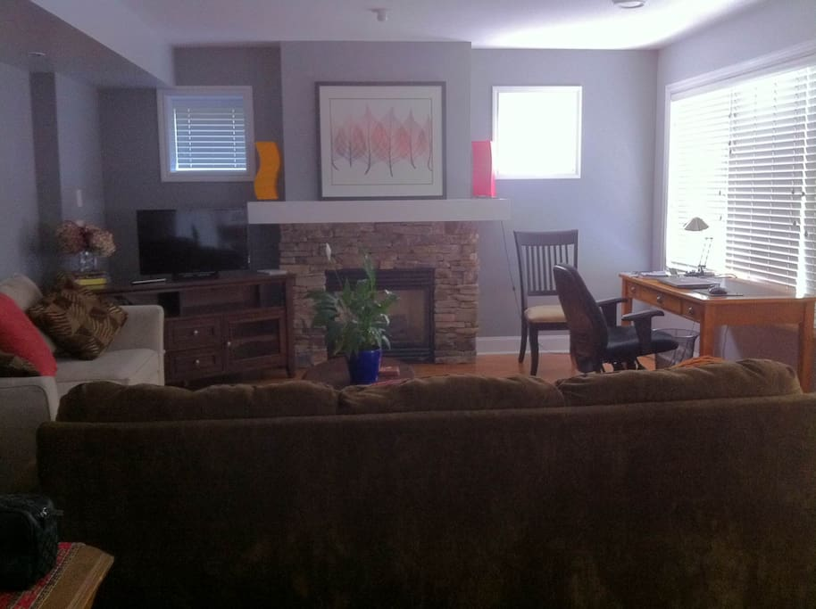 The living room lets the sun in! (In this photo the blinds are closed to reduce glare.) Desk is perfect for business travelers.  Window looks out to private deck and garden courtyard.