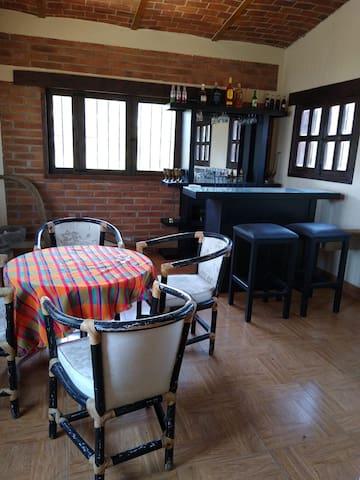 Sala de estar, segunda planta, con bar (sin bebidas) mesa de juego y salida al balcón.