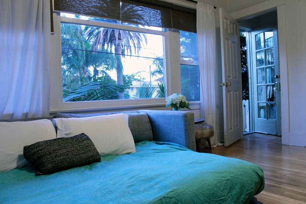 *NEWLY UPDATED*: New Queen pillow-top mattress has replaced the pull out couch! The window with a view of the palm trees. A small balcony peeps out to the neighborhood.