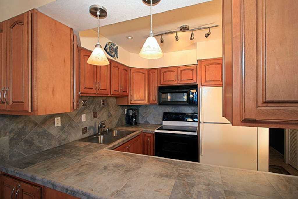 Complete newly remodeled kitchen with new tile countertops and appliances