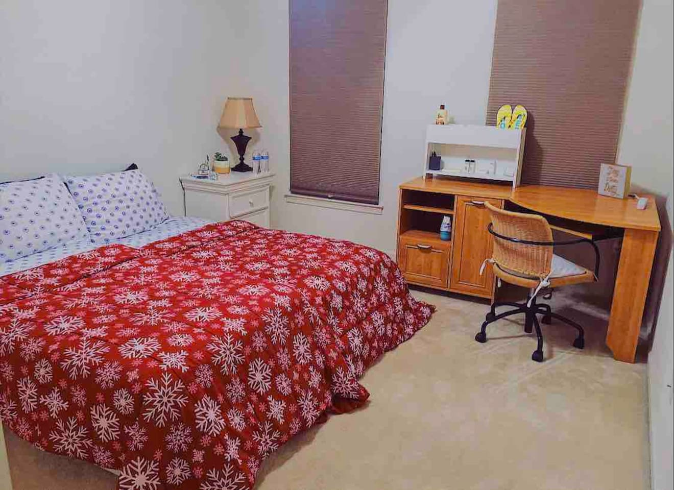 Cozy room with 2 twin beds, desk table, side table, lamp, organizer stand, and mini fridge