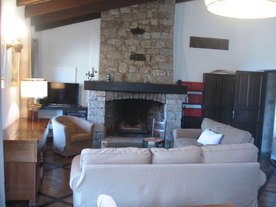 Un vaste séjour au coin de la cheminée en pierre.