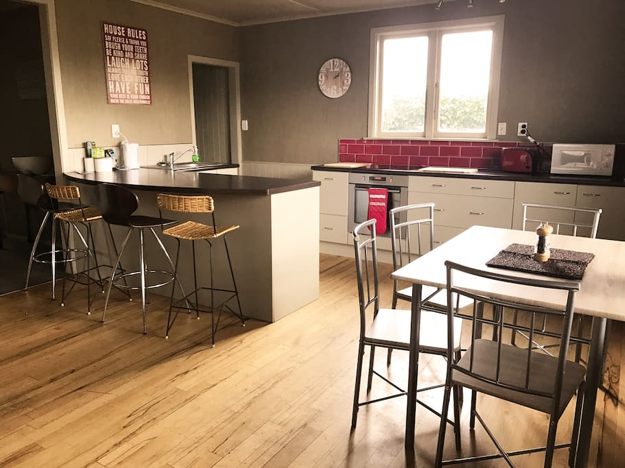 Modern open plan kitchen with stovetop, dining table, oven, fridge/freezer, dishwasher as well bar leaners