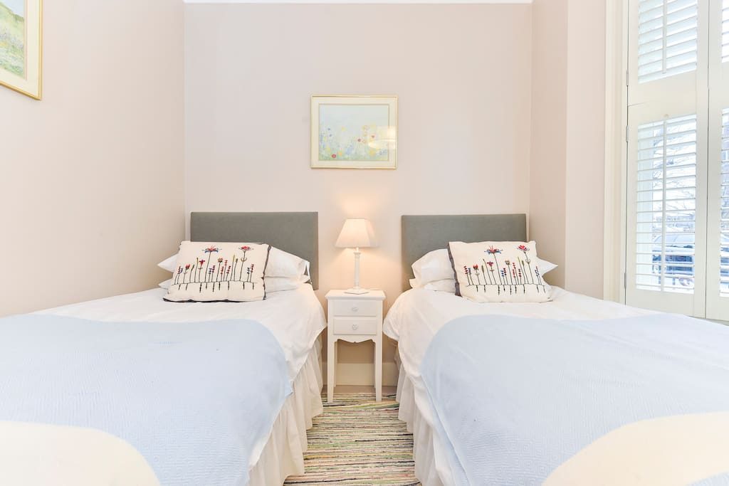 The second bedroom has twin single beds and a lovely bay window allowing lots of natural light into the room. There are solid shutters to block it out for a comfortable night's sleep! Linen and towels are provided.