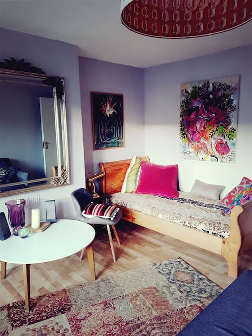 The sitting room with day bed and sofa bed, shabby chic furniture and collection of art