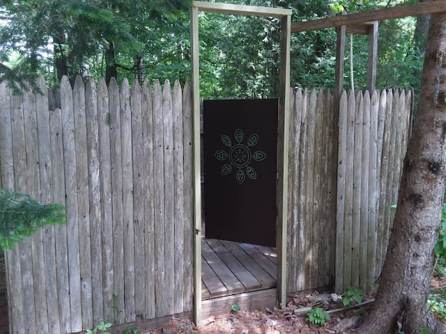 Enclosed outdoor hot shower with chair, clothing shelf, and towel hooks.