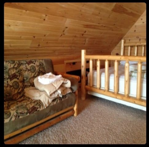 Loft bedroom with a futon sofa bed that sleeps two and two queen size beds that sleep two each with a beautiful view out of the top of the cabin looking right out to the water and over looking the kitchen and living room.