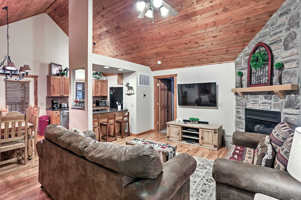 The open living space features vaulted wood ceilings, beautiful hardwood floors, and a charming stone fireplace.