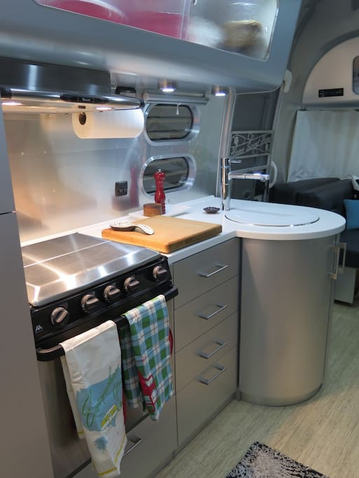 Kitchen with 3 burner stovetop, oven, sink, freezer/fridge and lots of storage