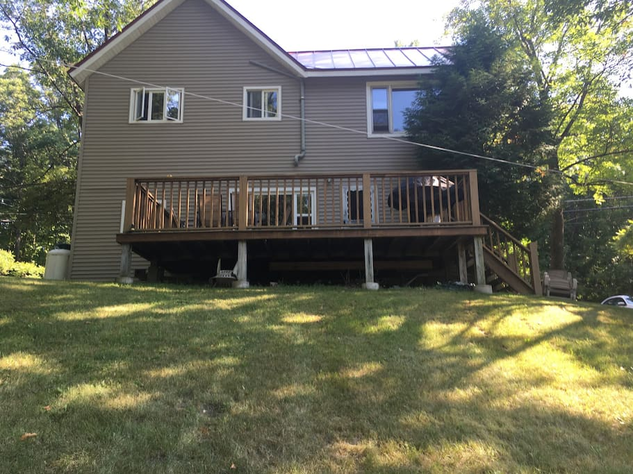Back deck and yard slopes down to stream