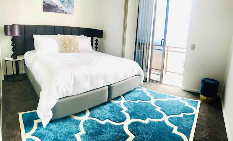 Another King Bedroom with a floor to ceiling sliding door that opens onto the upper balcony. Reverse Cycle Air conditioning and hues of blue to calm your mind and soul for A perfect night sleep.  The bed can be made into 2 singles if requested!