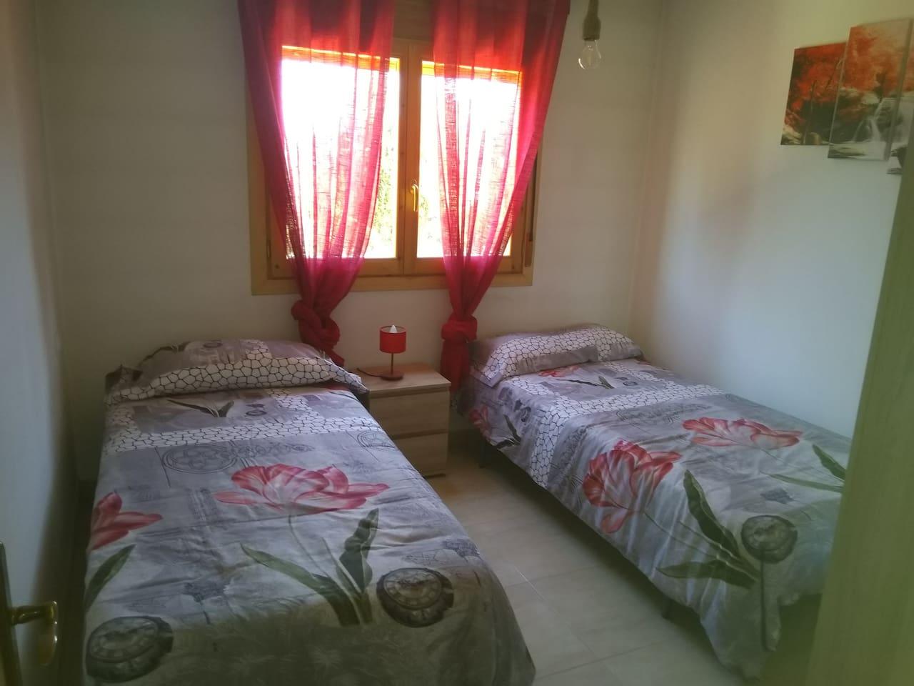 Cómoda habitación con dos camas individuales, mesilla de noche y amplio armario.