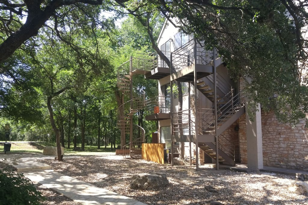 My building is surrounded by trees with a large grassy area in the back. A private spiral staircase serves as a back entrance to the patio.