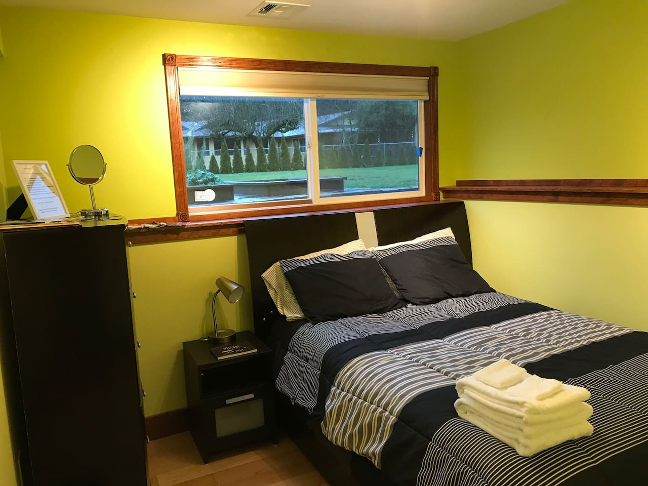 The green room gives off a refreshing feel with a window overlooking the backyard garden. The room includes dresser, closet with hangers, mirror, bedside lamp, space heater, and Washington State attraction pamphlets.
