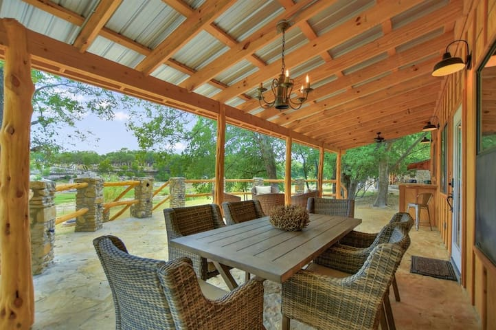 Riverfront patio with a dining table, bar area, and lounge seating to enjoy the views.