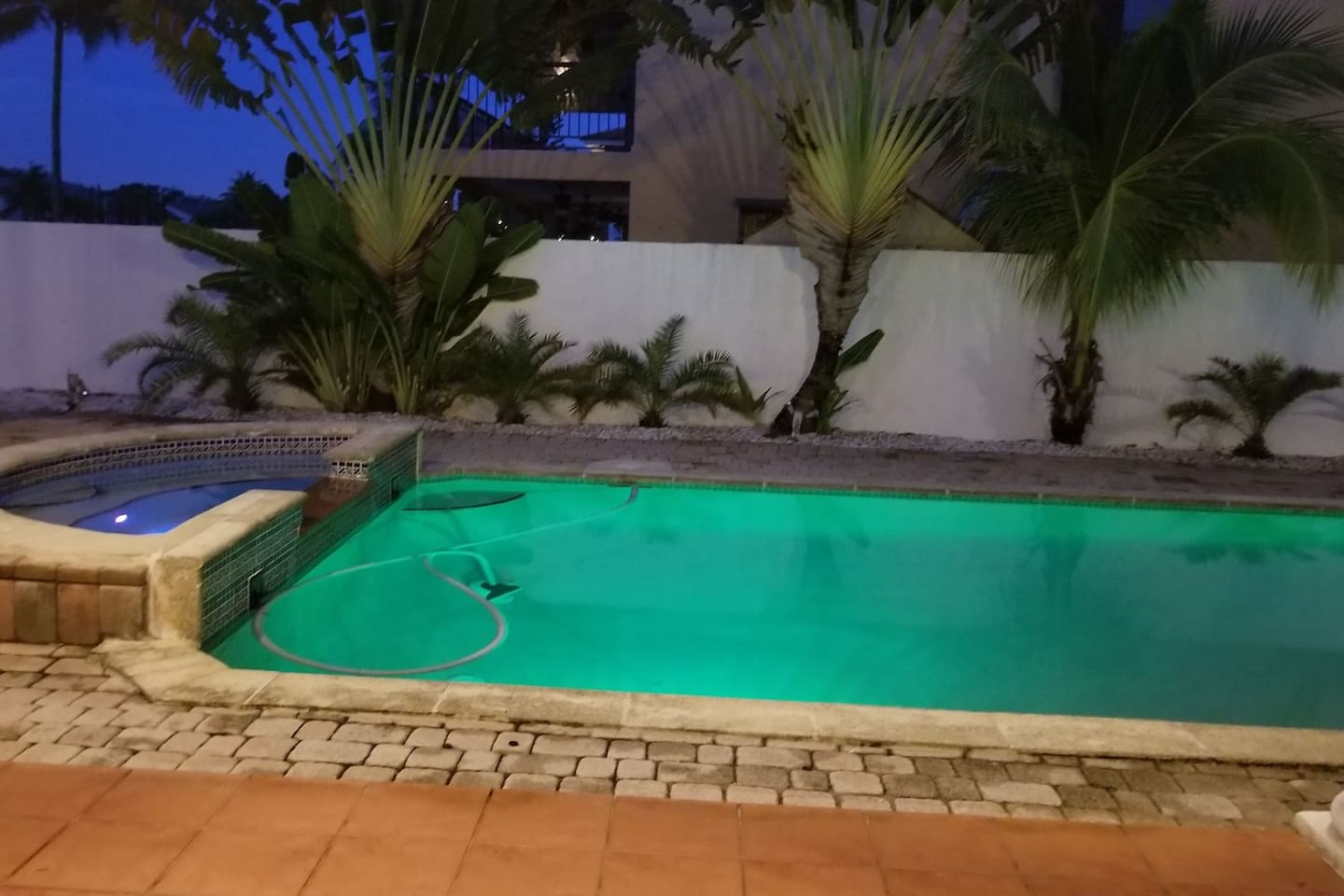 Pool and spa tub lit up at night