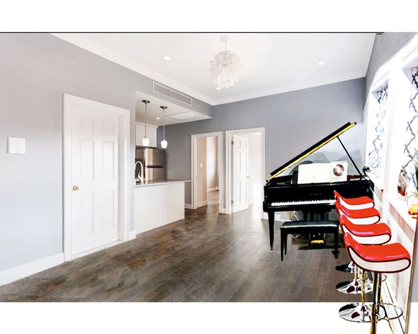 Gorgeous living room, with grand pianos, bar stools, sofa bed and all.