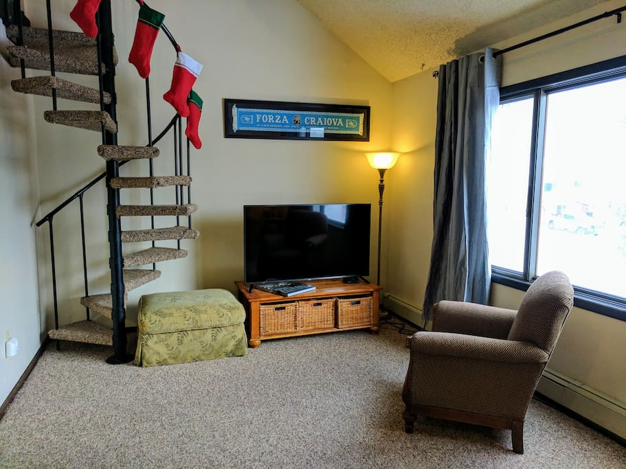 """We have a 55"""" LED TV with basic cable and Netflix. We have many board games in the wicker baskets beneath the TV. Stairs to the loft to the left."""