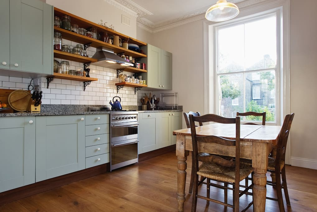 Kitchen with granite work surface and oak cupboards, shelves and floors.
