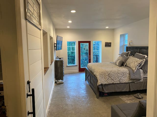 This is the Master Bedroom. The room has 2 interior windows that open to the great room. There is a King Bed and a couch that opens to a queen bed. A balcony has great views of the yard and forest below.