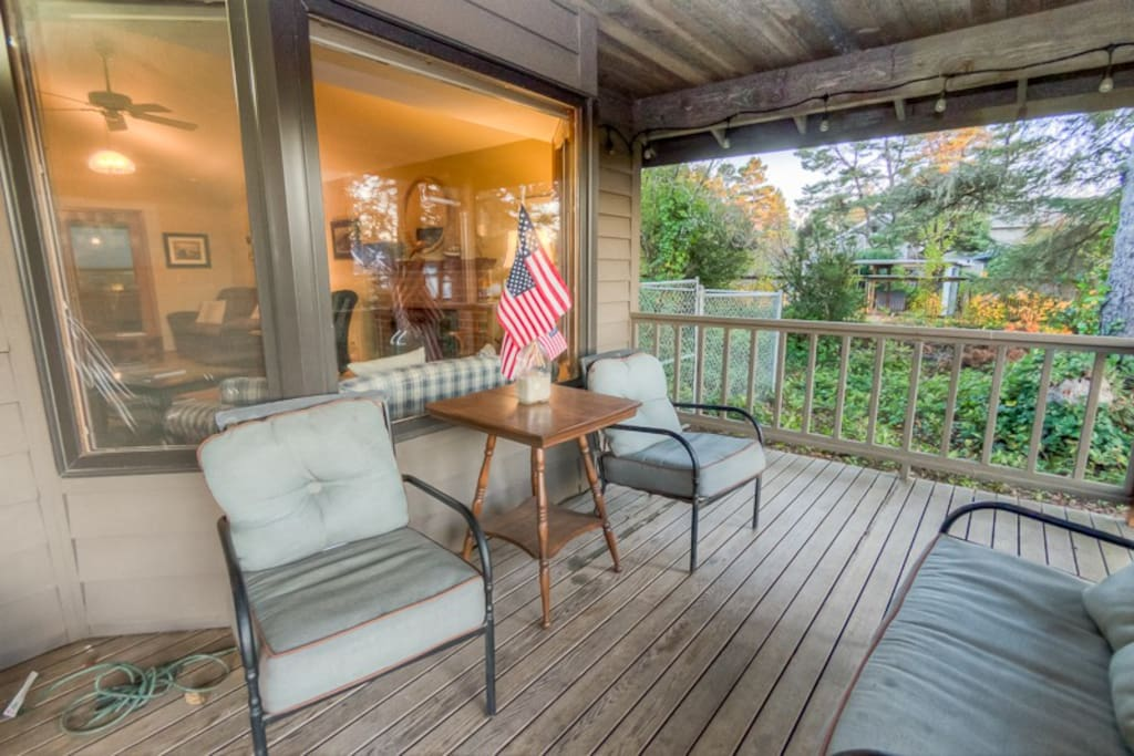 The covered porch has furniture to relax on.