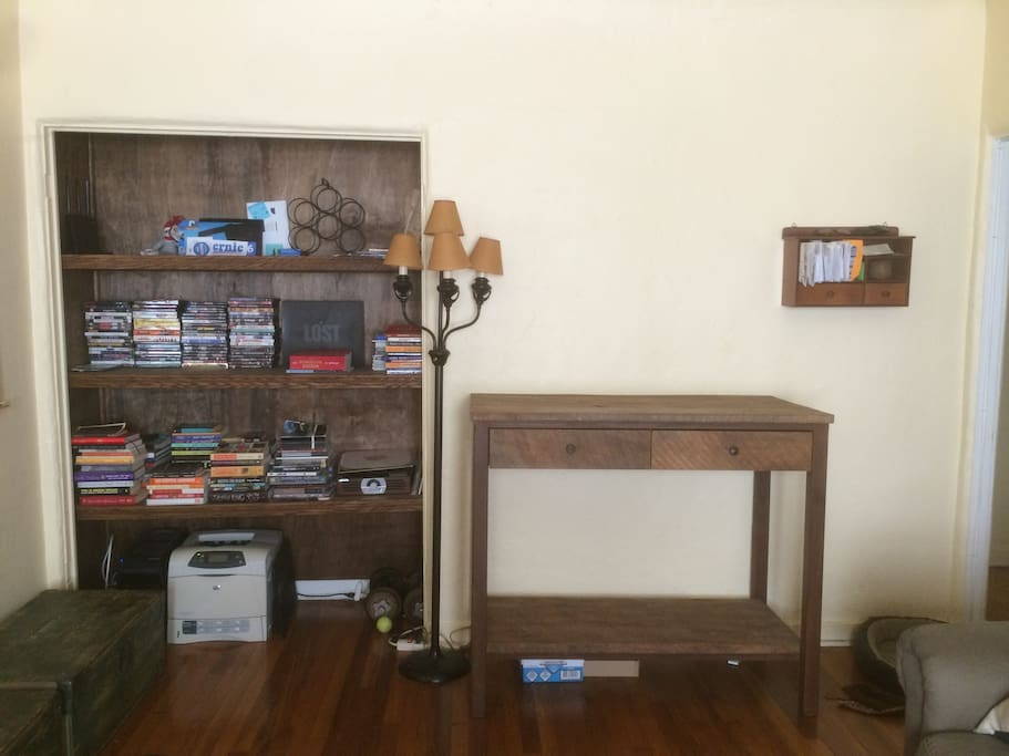 Standing desk and bookshelf with movies