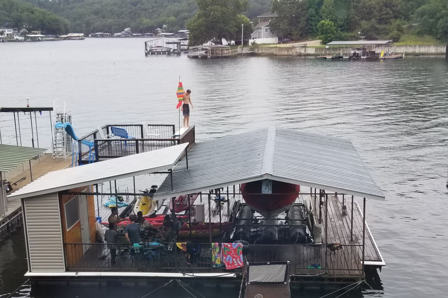 Killer dock with upper deck! So many activities to enjoy including swimming, a diving board, a new hammock chair (just installed), lily pad, two kayaks, covered entertainment area with table and chairs. Parking on sides of bumper-lined dock.