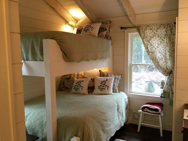 Warm, charming bunk room with larger full size mattress on bottom.  Whimsical Scalamandre curtains add a youthful touch.  Small closet, chest of drawers and a TV to stream movies or to play a DVD.  Stairs to top bunk provide storage and movies.