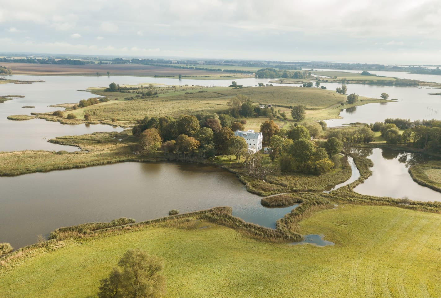Blick auf das Grundstück mit Herrenhaus und Wasserlandschaft