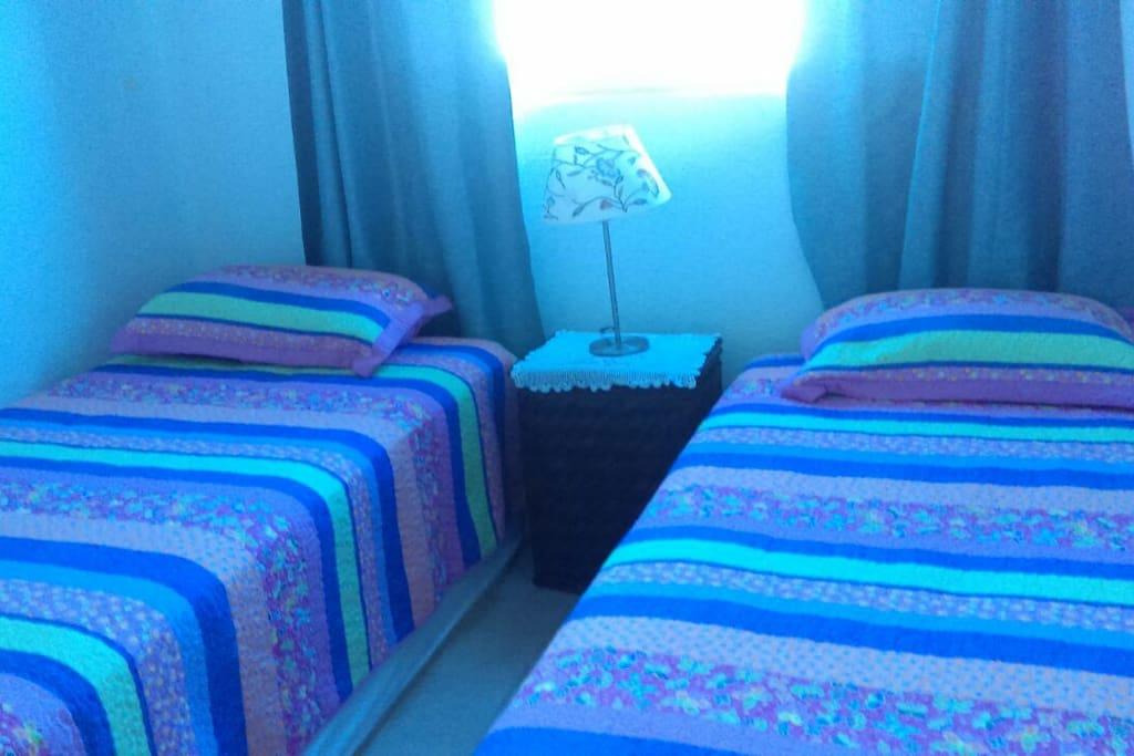Una habitación con dos camas individuales, ventilador y cajoneras