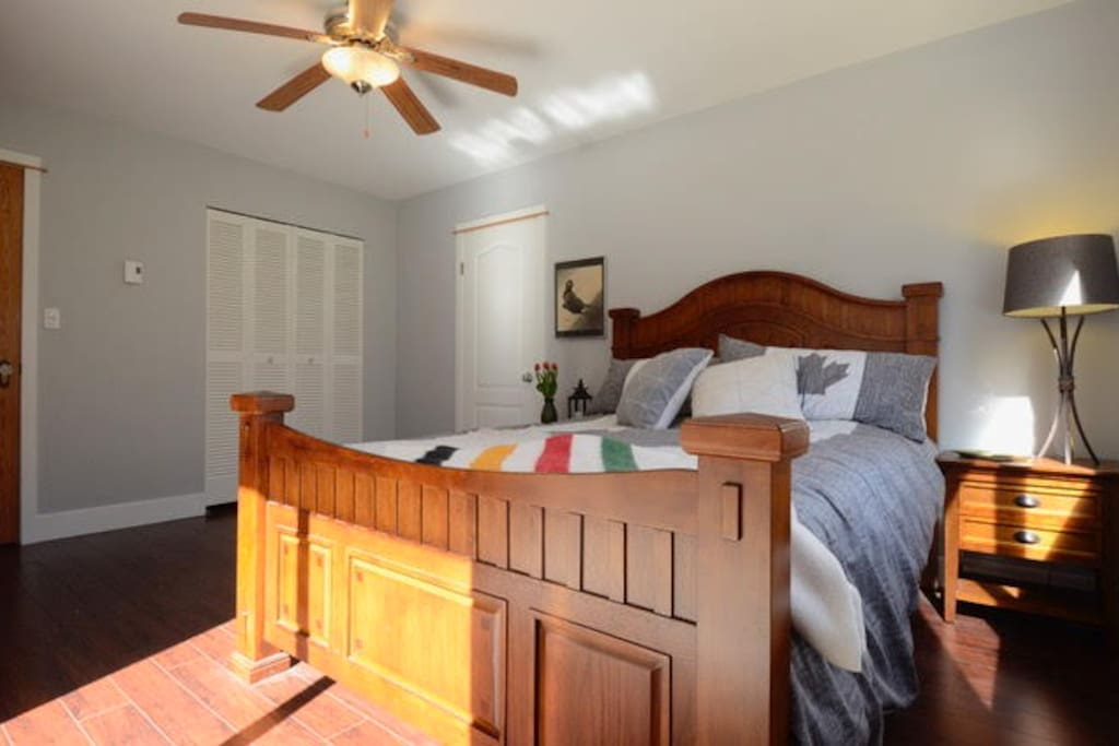 The romantic bedroom is complete with Canadian themed bedding, electric fireplace, television, sliding door with an incredible view of the apple orchard.