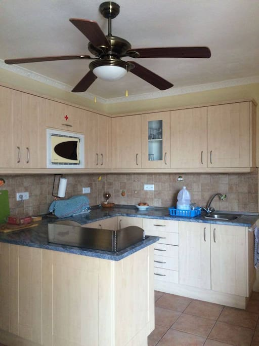 Kitchen with cooker, hob, sink, microwave and utensils