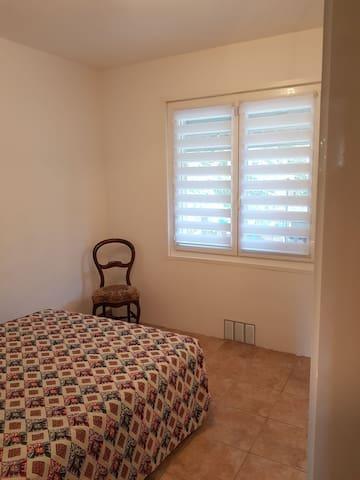 Chambre 3 avec lit double, la fenêtre donne sur la partie terrasse couverte de la maison