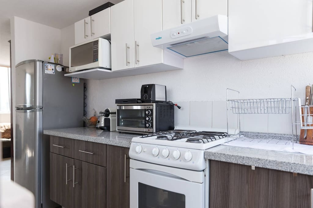 Cocina completa con estufa, horno de microondas, horno eléctrico, tostador, cafetera, refrigerador.