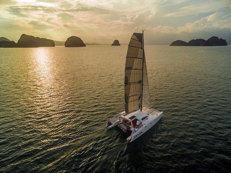 Private sailing into the sunset with a view of Thailand's gorgeous seascapes.