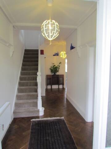 Traditional wide hallway with restored parquet flooring and Victorian features.