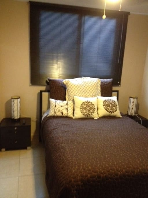 "Master bedroom in apartment with new double sized bed for 2 people with 2 night tables with lamps and with  32"" wall mounted cable TV, air conditioner and ceiling fan."