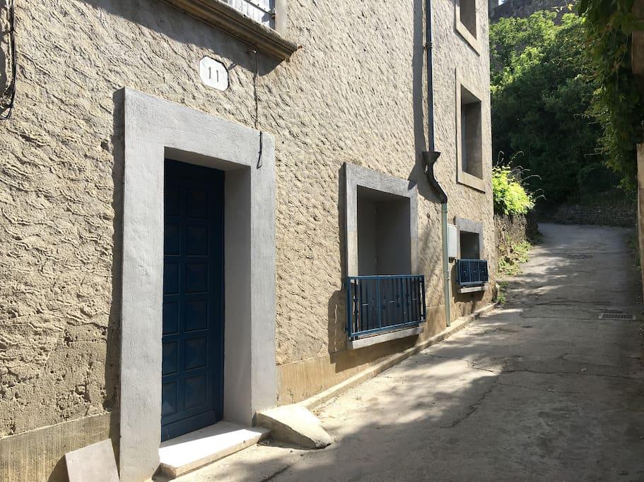 Côté remparts , la façade de la maison et le début du sentier pour aller à la cité