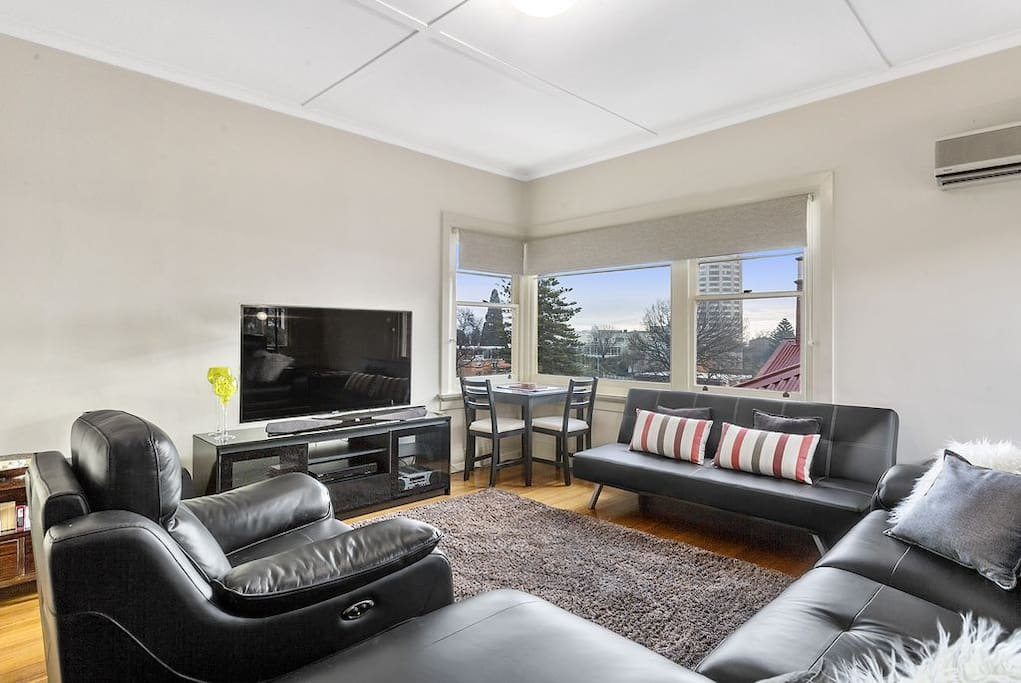 Living room with a stunning view of Wrest Point Casino, modern television, heat pump and electric recliner couches...