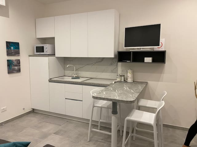 Cucina arredata con fuochi ad induzione, microonde, lavastoviglie, stoviglie e padelle.