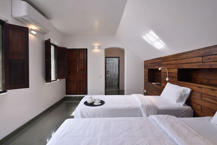 Bedroom with twin beds setup, front windows and attached bathroom