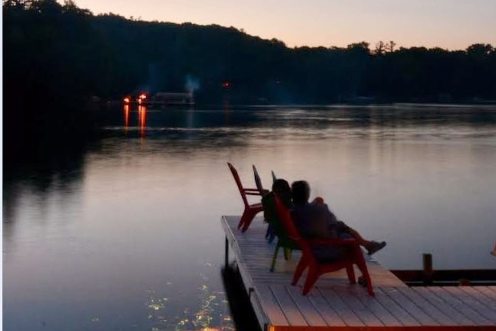 large lakeside deck and dock with floats, sand toys, chairs and picnic table.