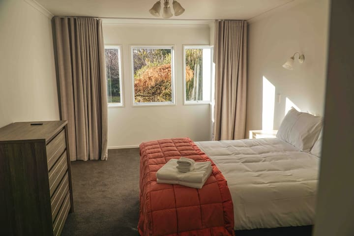 Downstairs bedroom with Queen bed, wardrobe and tallboy drawers