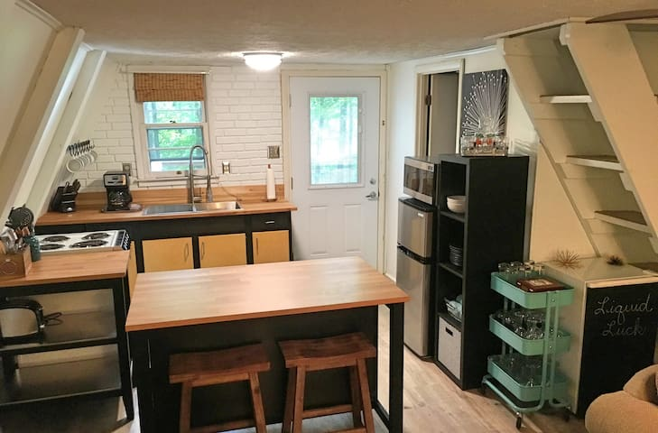 Open kitchen with compact fridge and freezer, additional beverage mini-fridge, stove with range, microwave, coffee maker, and toaster